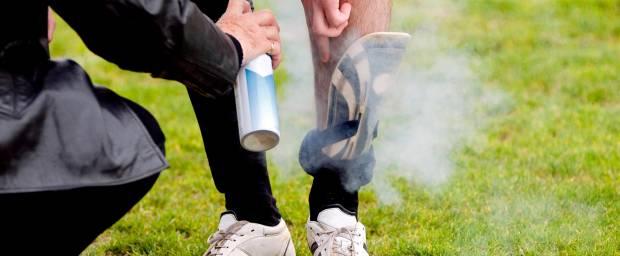 Fußballspieler wird mit Eisspray an Schienbein behandelt