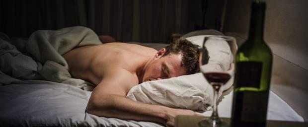 Schlafender Mann mit Alkohol am Bett