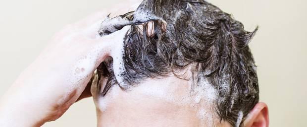 Mann wäscht sich die Haare mit Shampoo