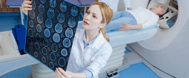 Junge Radiologin schaut sich MRT-Aufnahmen an