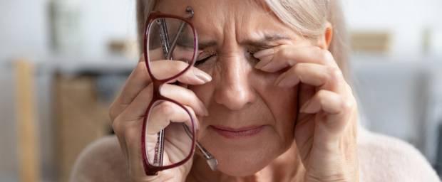 Ältere Frau mit Kopfschmerzen und Händen vor den Augen