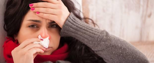 Frau mit Sinusitis und Kopfschmerzen im Bett