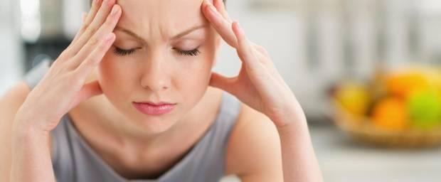 Frau mit Kopfschmerzen hält sich den Kopf