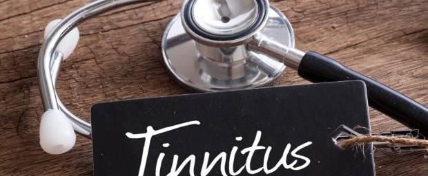 Stethoskop auf Holztisch liegend mit einem Täfelchen mit der Aufschrift Tinnitus