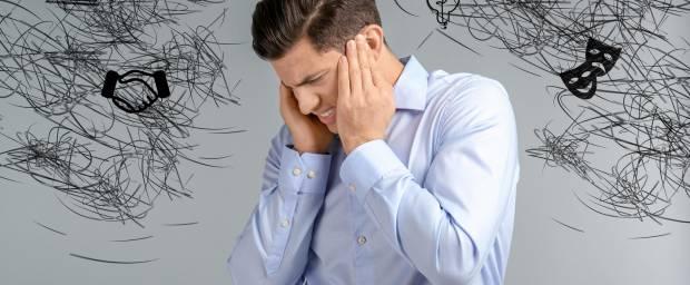 Mann hält sich den Kopf, weil er Stress hat
