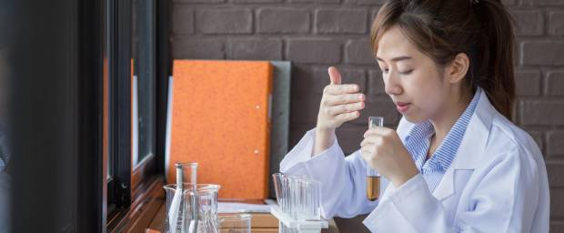 Asiatin riecht im Chemielabor an einem Reagenzglas
