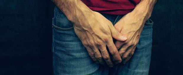 Mann umfasst sein Geschlechtsteil mit beiden Händen
