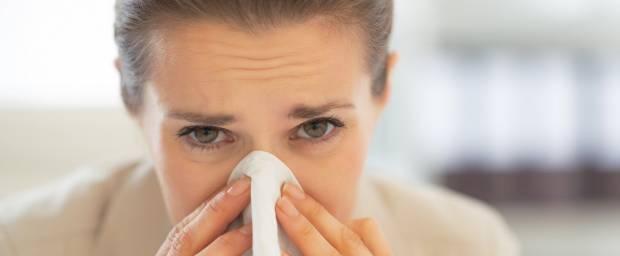 Frau putzt sich die Nase mit Taschentuch