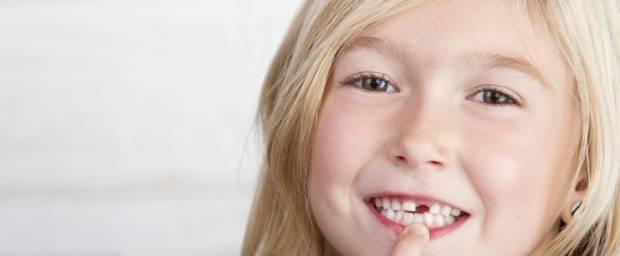 Junges Mädchen zeigt auf Ihre Zahnlücke im Mund