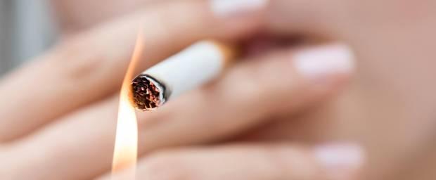 Frau zündet sich eine Zigarette an