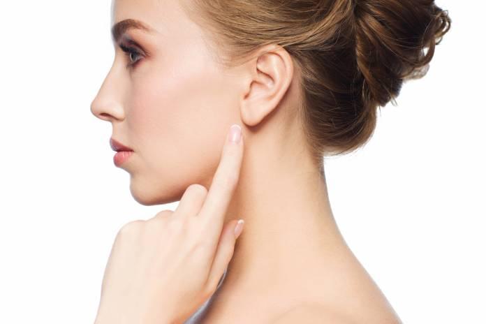 Frau im Profil zeigt auf Ohr