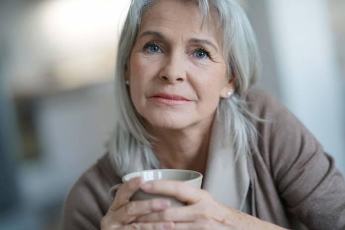 Ältere Frau mit Tasse in der Hand