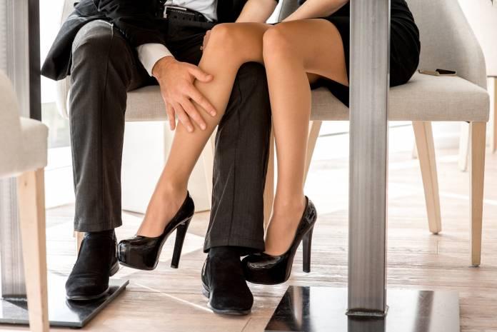 Mann streichelt Frau über das Bein