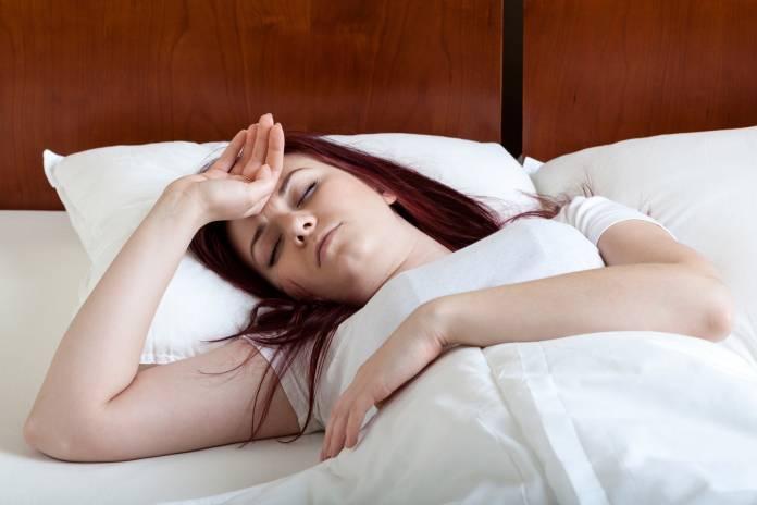 Junge Frau liegt mit Fieber oder Kopfweh im Bett